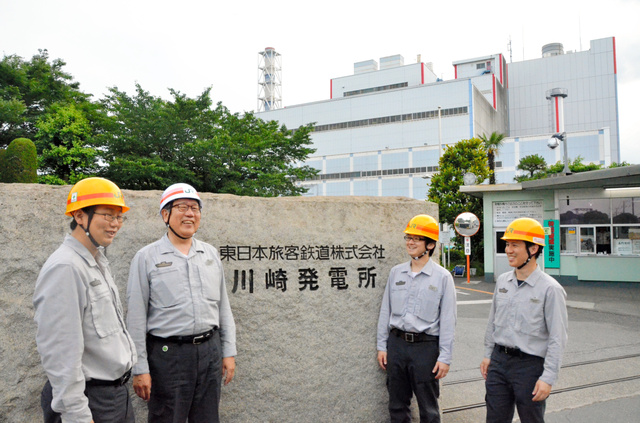 JR東日本の川崎発電所前に立つ大井昭彦所長(左から2人目)と若手職員たち=川崎市川崎区扇町