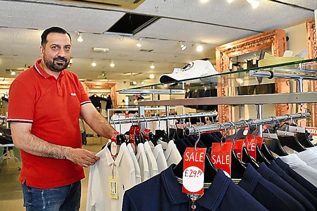 衣料品店で商品をととのえるモハメド・アリさん。店の売上高は1年前と比べて1割ほど減ったという=ロンドン、寺西和男撮影