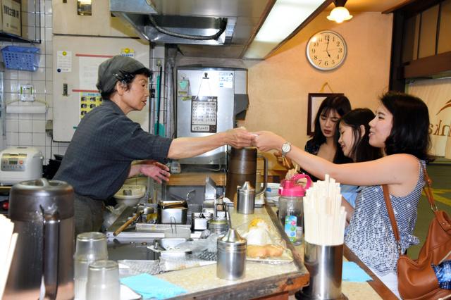 商品を渡す淡路しづ代さん(左)=南海和歌山市駅
