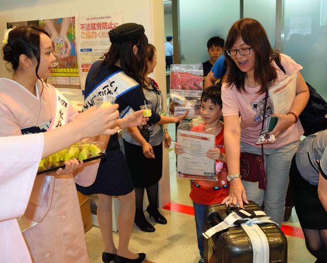 到着口で記念品やメロンを受け取る台湾からの搭乗客=茨城空港