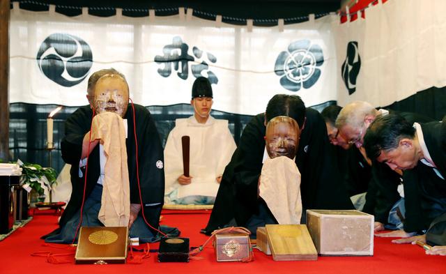 室町時代に作られた本面(左)と江戸時代に作られた写し面を確認する保存会の役員ら=京都市下京区、佐藤慈子撮影
