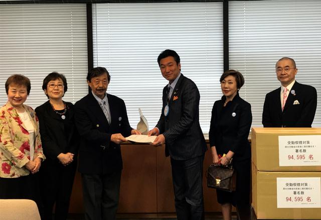 日本禁煙学会の作田学理事長(左から3番目)が橋本岳副大臣(右から3番目)に署名を手渡した=東京・霞が関の厚生労働省