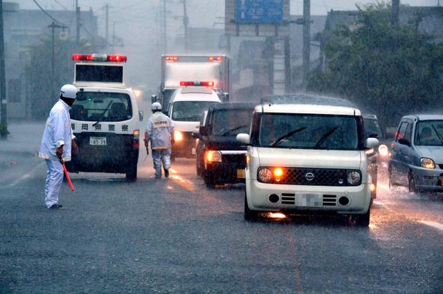 氾濫した桂川近くの386号では警察がたち、警戒していた=5日午後5時20分、福岡県朝倉市宮野、福岡亜純撮影