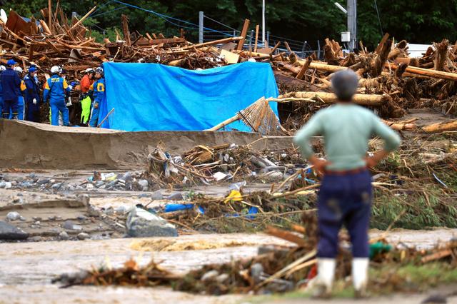 倒木が押し寄せた場所を捜索する警察官ら=7日午後5時34分、福岡県朝倉市杷木林田、長島一浩撮影
