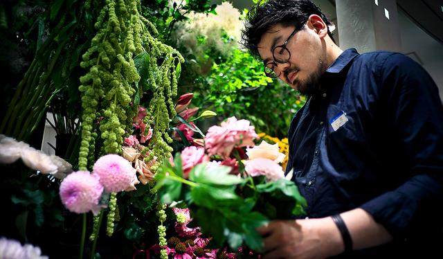 若いスタッフには飾り付けやブーケ作りを教えて育てる。「花屋の成長は階段状。滑らかに伸びるのではなく、一段一段登るイメージ」=東京都渋谷区、村上健撮影