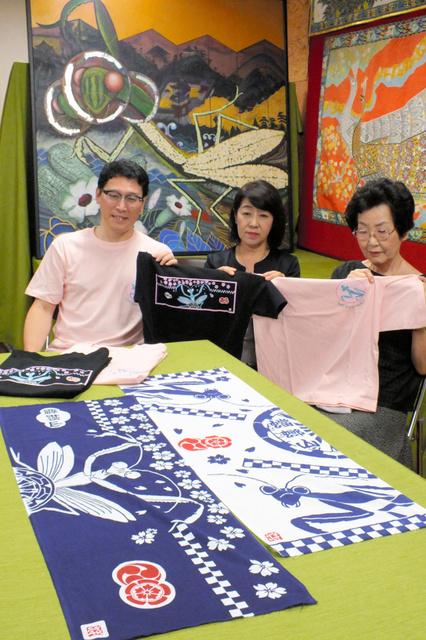 蟷螂山の手ぬぐいやTシャツをデザインした画家の森田洋子さん(中央)。左奥のカマキリを描いた絵は森田さんの作品=京都市中京区