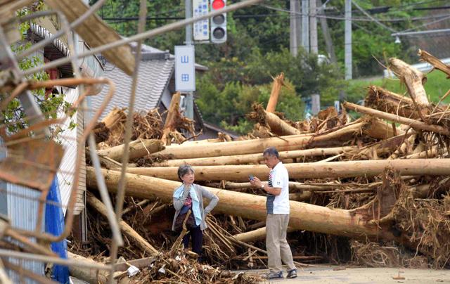 山田地区の交差点に流れ着いた流木はいまだに撤去出来ず、道路をふさいでいた=11日午前9時45分、福岡県朝倉市山田、長沢幹城撮影