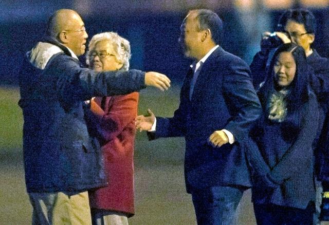 2014年11月8日、米ワシントン州の空軍基地で家族との再会を喜ぶケネス・ベー氏(左)=ロイター