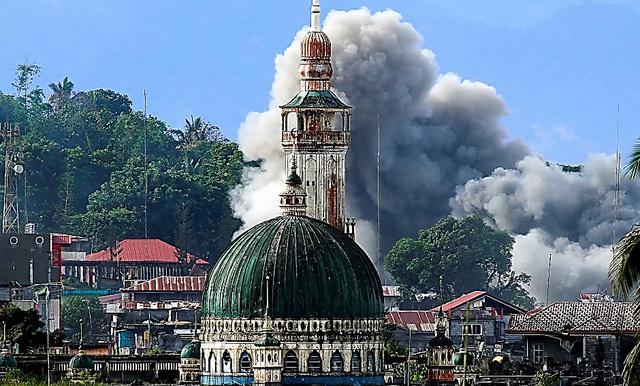 フィリピン軍の空爆で黒煙が上がった。ミンダナオ島では、ISに忠誠を誓う組織と軍の戦闘が続く=6月29日、ロイター