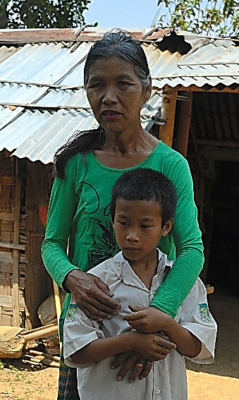 「娘に会いたい」。自宅の前で話すカウンツィンさん。長男と=ミャンマー・ラショー近郊