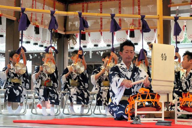 復元した鉦をたたく鷹山保存会の子どもたち。右手前は焼け残った鉦=京都市東山区の八坂神社