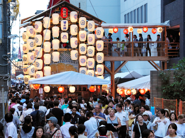 駒形提灯がともる中、山鉾巡りを楽しむ人たち=14日午後6時42分、京都市下京区、佐藤慈子撮影