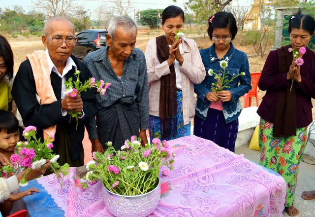慰霊祭の後に花を供えるエイモンさん(左端)ら村人たち=3月8日午前8時半、ミャンマー・ウェトレット村、大久保真紀撮影
