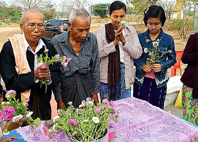 慰霊祭の後に花を供えるエイモンさん(左端)ら村人たち=3月8日、ミャンマー・ウェトレット村