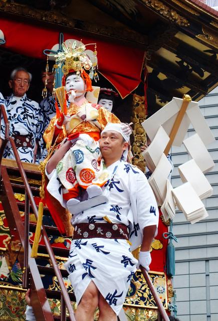 強力の肩に担がれたまま、長刀鉾に乗り込む稚児=17日午前9時、京都市下京区、大村治郎撮影