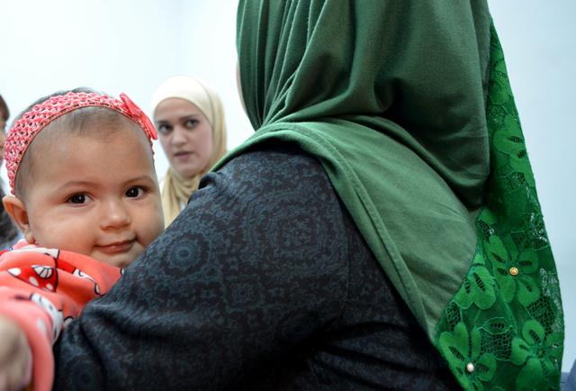 娘のガザルちゃんを抱いてカウンセラーと話す17歳の少女(右)=ヨルダン・ザルカ、大久保真紀撮影