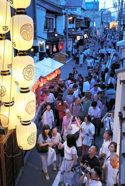 後祭の宵山期間が始まり、駒形提灯に明かりが灯った南観音山を見上げる人たち=21日午後7時1分、京都市中京区、佐藤慈子撮影