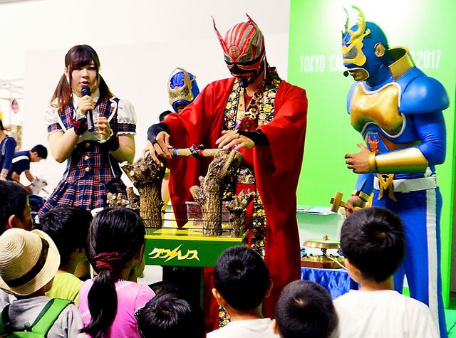 ミヤマ☆仮面(右)とクワガタ忍者(中央)による昆虫ショー。左は司会の垣原綾乃さん=2日、東京都江東区