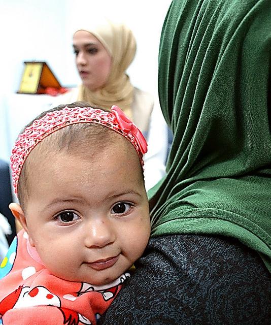 「3カ月前にやっと離婚が成立した」。娘のガザルちゃんを抱く17歳の少女(右)=ヨルダン・ザルカ