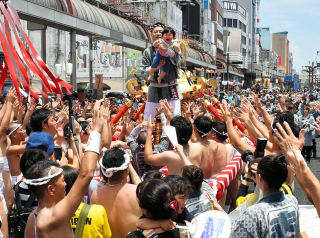 みこしの上に子どもを担ぎ上げ、健やかな成長を祈った=鹿児島市
