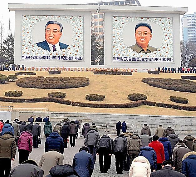 金正日総書記の死去5年を迎えた2016年12月17日、金日成主席と金総書記の肖像画が描かれた壁画の前で黙祷(もくとう)する平壌市民=朝鮮通信