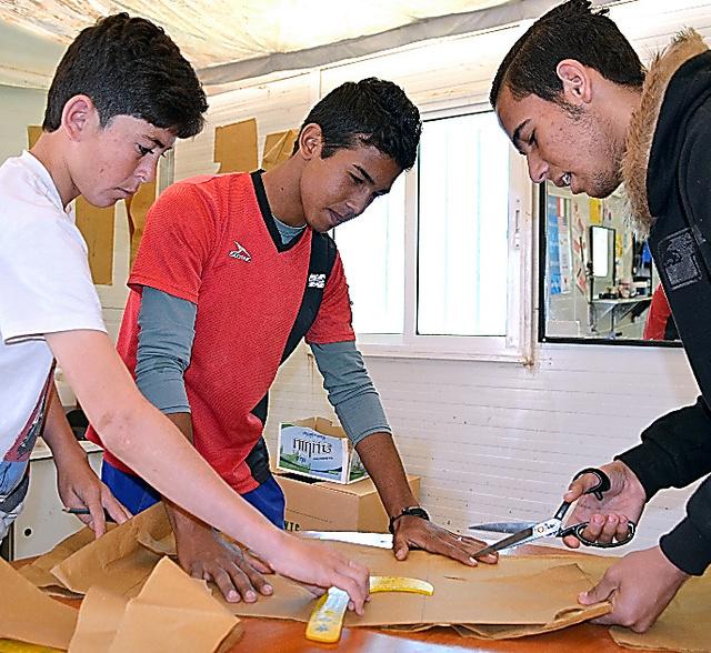 型紙の切り方を学ぶディア君(中央)。「仕立屋になって家族を養いたい」=ヨルダン・ザアタリ難民キャンプ
