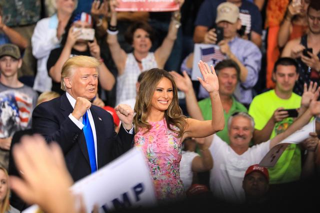 集会で支持者らにガッツポーズを見せるトランプ米大統領(左)と手を振るメラニア夫人=25日、オハイオ州ヤングスタウン、ランハム裕子撮影