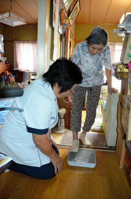 体重を測る昭子さん。訪問看護師がチェックする=7月11日、兵庫県姫路市