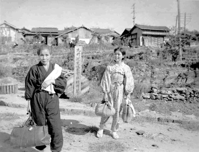 笑顔を見せる女性。背後の立て札には「九州配電株式会社材料置」の文字が見える(ジョン・オーウェン・メイ氏撮影、長崎原爆資料館提供)