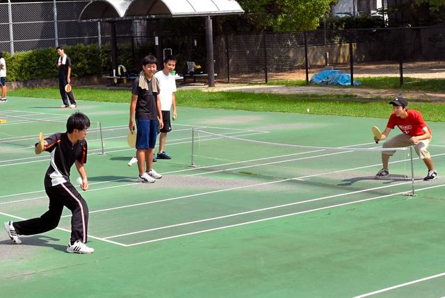 エスキーテニス専用コートで練習に励む大学生ら=広島市東区の新牛田公園
