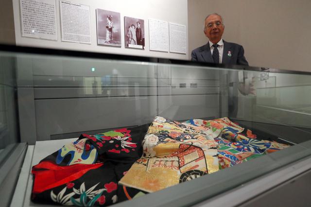 展示されている母・稔子さんの婚礼衣装と飯田国彦さん=7月15日午後、広島市中区の平和記念資料館、上田幸一撮影