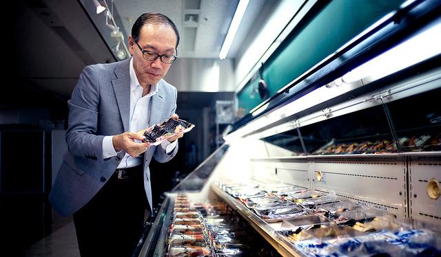 社内に設けた陳列棚の前で、開発したトレーを確かめる。「消費者に無意識に手に取ってもらえる容器づくりを目指しています」=東京都新宿区の東京本社、村上健撮影