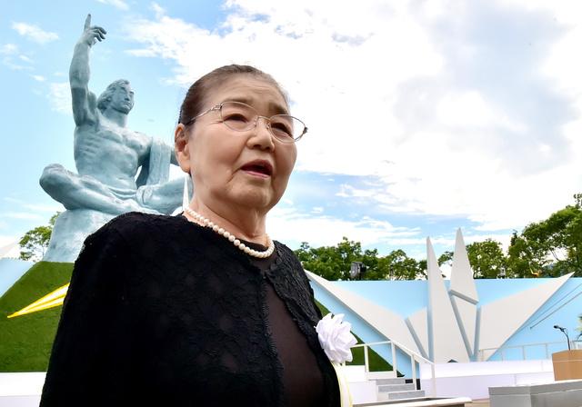 平和祈念像の前に立つ福井絹代さん=昨年8月9日、長崎市松山町の平和公園