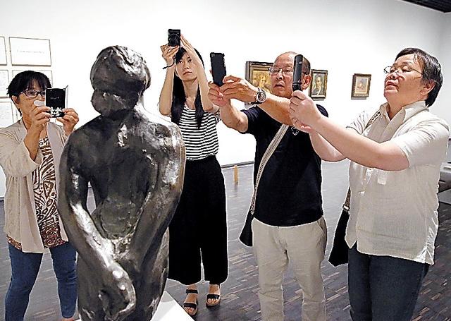 彫刻作品を撮影する参加者たち=鬼室黎撮影