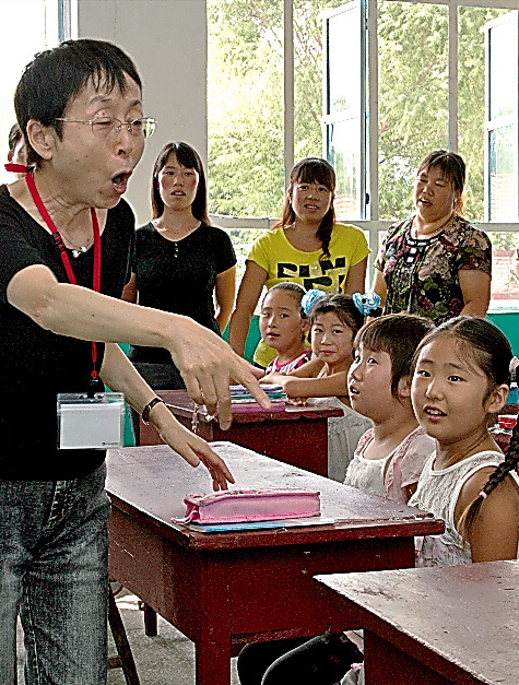 中国の子どもたちに輪唱を教える旅の参加者=2010年8月、「中国・山地の人々と交流する会」提供