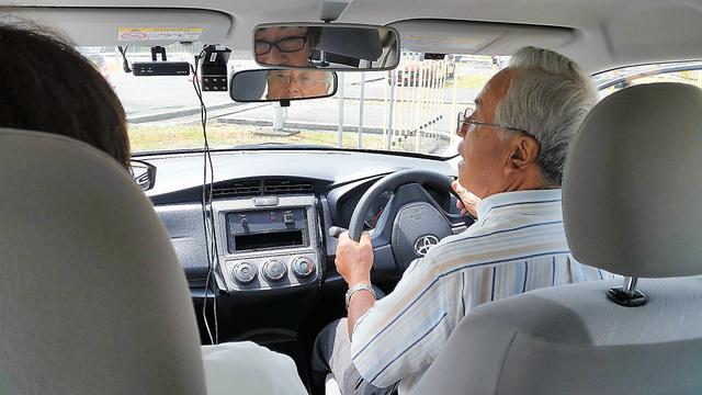 教習車をバックさせる受講者。バックミラーの左右に車内外の動画を記録するドライブレコーダーがある=下関市の下関自動車学校