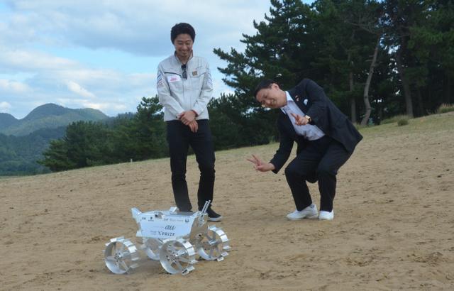 ハクトの袴田代表(左)から説明を受け、試作機のカメラに向かってポーズをとる平井知事=鳥取市浜坂