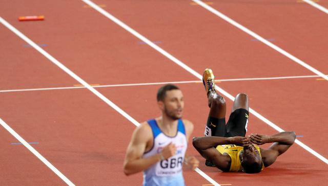 男子400メートルリレー決勝で足を痛めトラックに転倒するボルト(右)。左上はバトン=池田良撮影