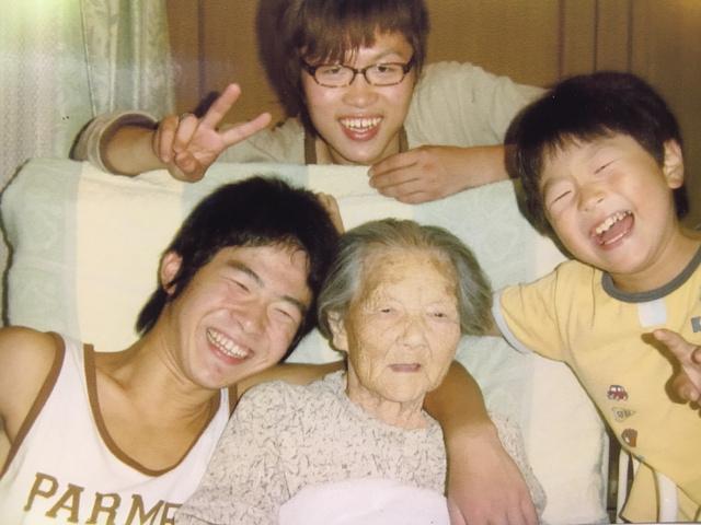 投稿者の村上英子さんの祖母市毛とよさん(中央)のベッド脇に集まる村上さんの3人の子どもたち=2004年、村上さん提供