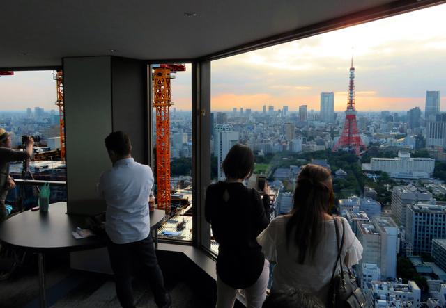 世界貿易センタービルの展望台で撮影する人たち。日没から夜が最もにぎわう=東京都港区