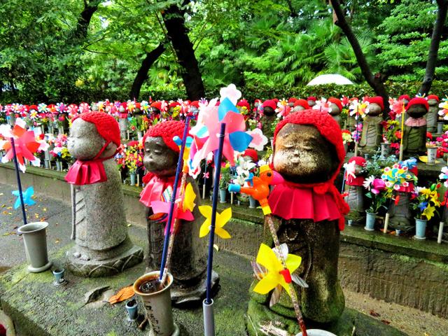 増上寺の境内に立つ子育て地蔵。お供えの花や風車の色鮮やかさが目を引く=東京都港区