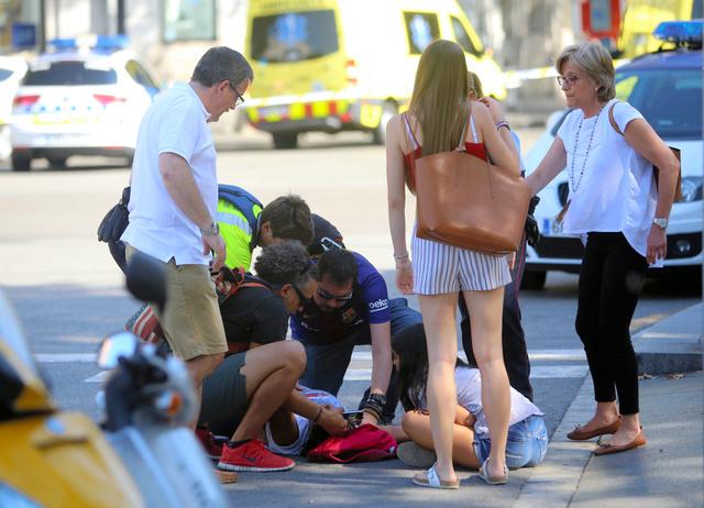 スペイン・バルセロナのランブラス通りで17日、車が歩道に突っ込み、けがの手当てを受ける人=AP