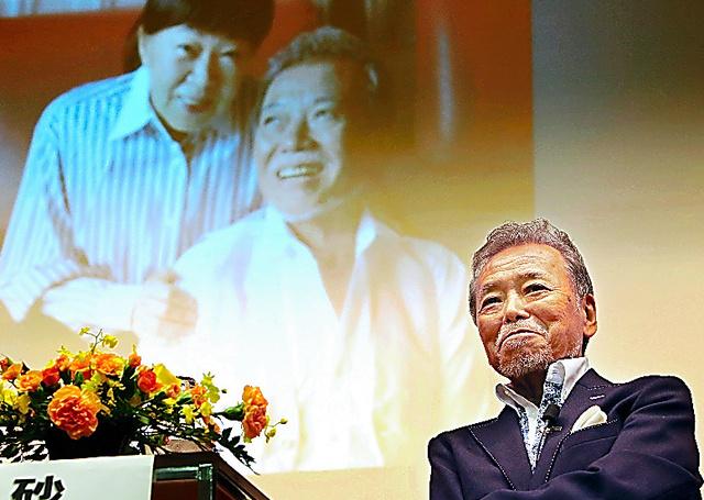 妻の大山のぶ代さんと撮影した写真のスライドを背に話す砂川啓介さん=2016年6月