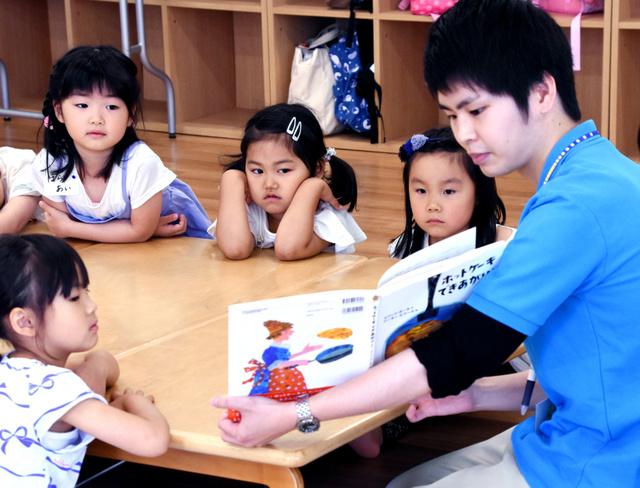 民間学童で開催された未就学児向けのイベント。スタッフが絵本を読む=東京都練馬区