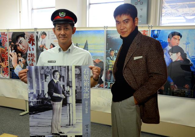 等身大の裕次郎パネルと過去に発売された大型の記念入場券=JR小樽駅
