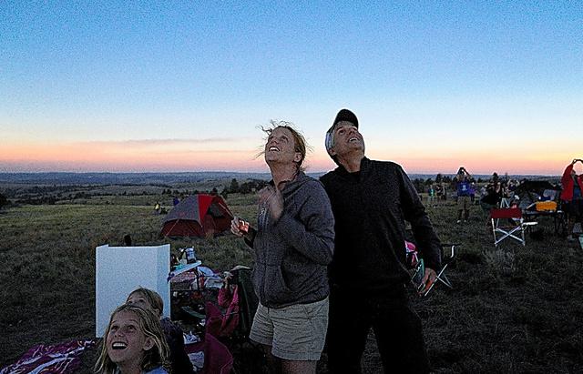 ワイオミング州で、皆既日食を見上げる人々=ロイター