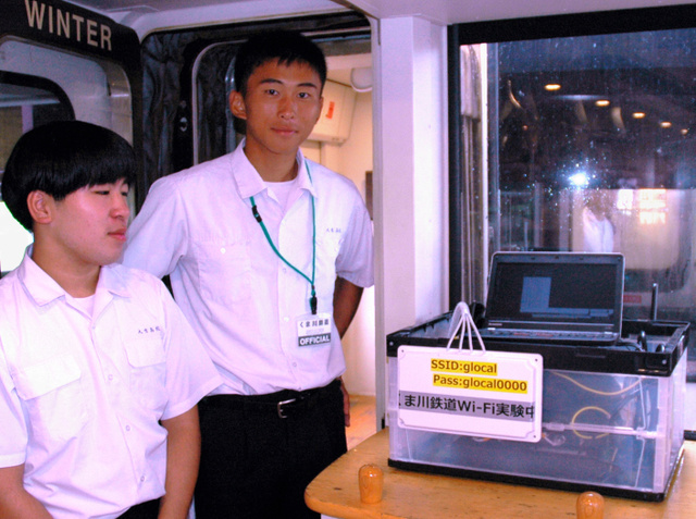 くま川鉄道車内に置いた「Wi―Fi(ワイファイ)」設備の脇に立つ森下将剛さん(右)=人吉市