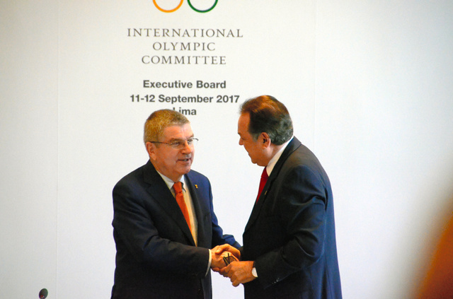 IOC理事会の前にペルー五輪委のデル・ロサリオ会長(右)と握手を交わすIOCのバッハ会長