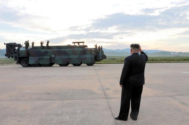 北朝鮮の金正恩・朝鮮労働党委員長が中距離弾道ミサイル「火星12」の発射を現地指導したとして、朝鮮中央通信が16日、配信した写真=ロイター。奥はミサイルの移動式発射台