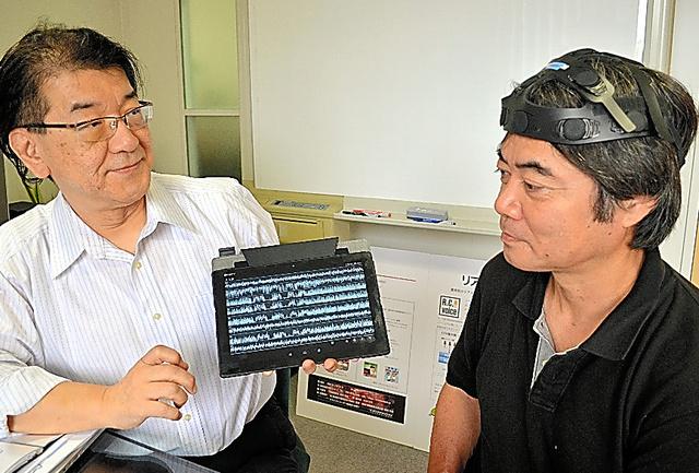 ブレインメロディのデモンストレーションをする飛河和生社長(左)ら。測った脳波が端末に表示されている=東京都世田谷区